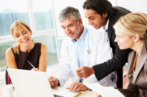 business team looking at laptop with doctor